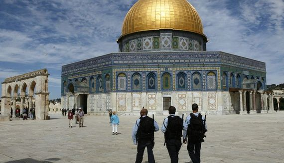 Israeli police officers walk in front of the Dome of the Rock, on the Temple Mount.